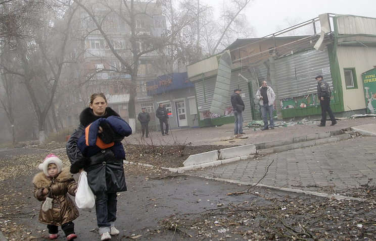 Residents near damaged building after shelling in Donetsk region