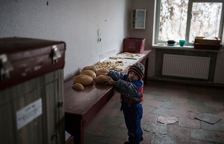 A boy holds bread in a town in Luhansk region