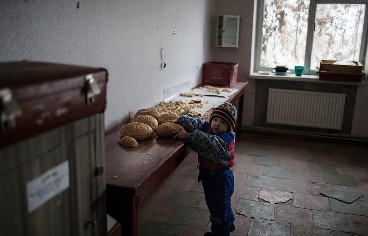 A boy holds bread in a town in Luhansk region