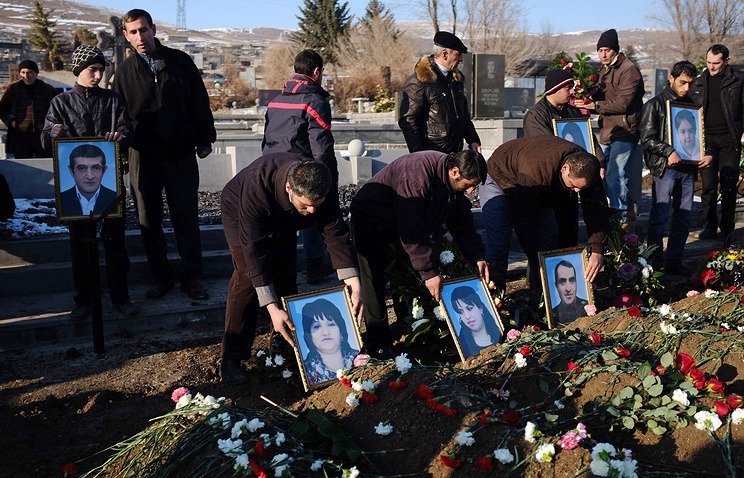 People holds portraits of six dead members of the Avetisyan family during a funeral in the city of Gyumri, Armenia