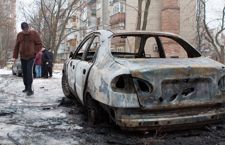 A burnt out vehicle on a street of Donetsk
