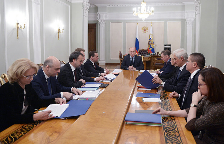 Vladimir Putin (center) in a meeting over economic issues
