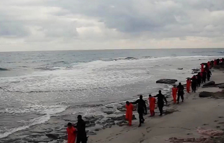 Egyptian Coptic Christians in orange jumpsuits being led by Islamic State militants along a beach in Libya