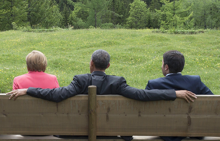 German Chancellor Angela Merkel, US President Barack Obama and Italy's Prime Minister Matteo Renzi sitting on a bench during the G7 summit
