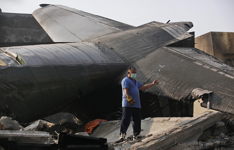 A rescuer stands near the wreckage of an Indonesian Air Force cargo plane that crashed in Medan, North Sumatra, Indonesia, Tuesday, June 30, 2015