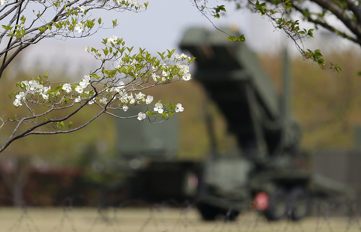 Flowers are in bloom against a backdrop of a PAC-3 missile interceptor deployed in Japan
