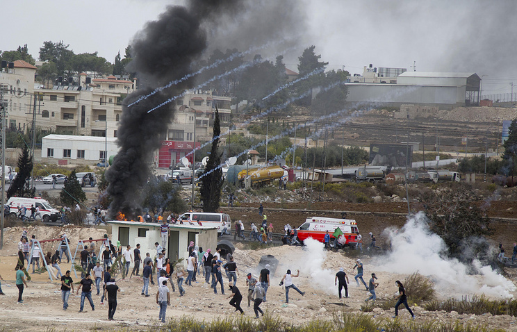 Palestinian protesters running for cover from tear gas fired by Israeli soldiers during clashes with Israeli troops near Ramallah