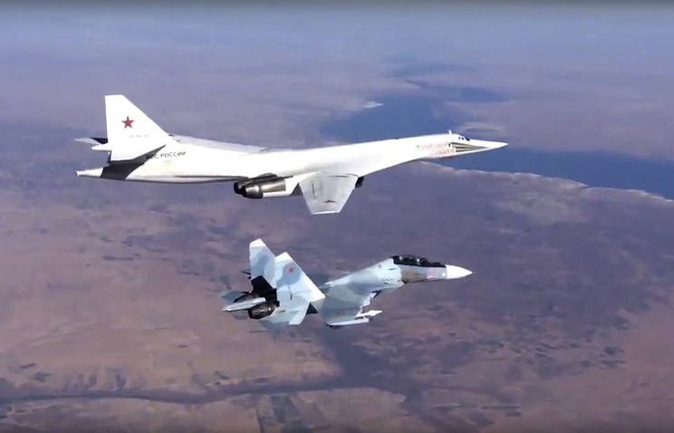Russian Tu-160 bomber, top, is escorted by an Su-30SM fighter
