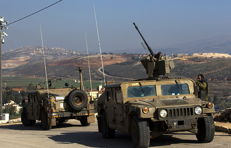 Israeli soldiers guard nea a Lebanese village on the Israeli-Lebanese border
