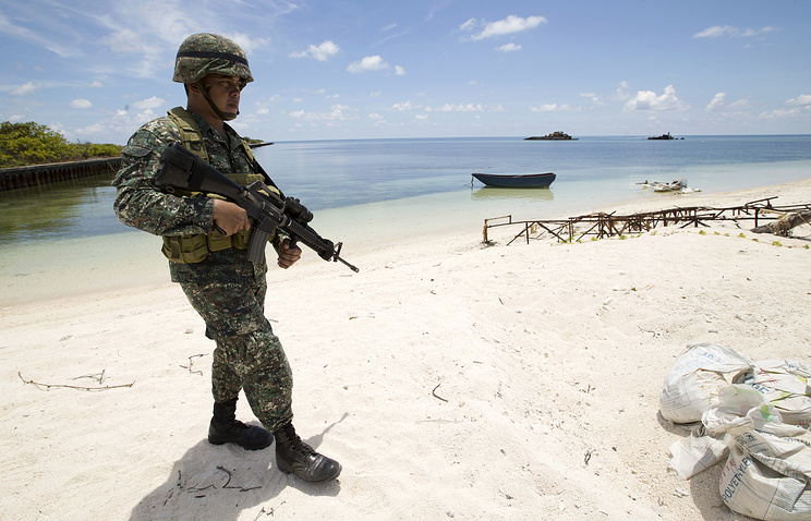 Filipino soldier patroling the shore of Pagasa Island