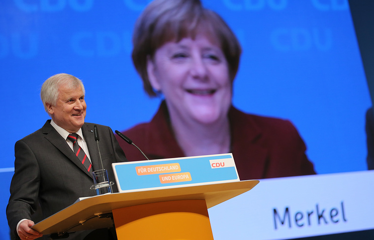German Chancellor Angela Merkel is seen on a video screen during the speech of Bavarian Governor Horst Seehofer during the Christian Democratic, CDU, party convention in Karlsruhe, Germany, December 15, 2015