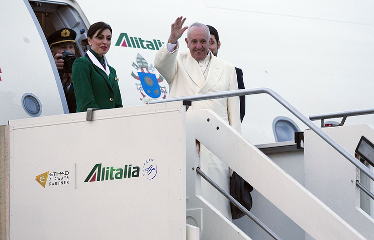 Pope Francis waves as he boards an airplane at Rome's Fiumicino airport