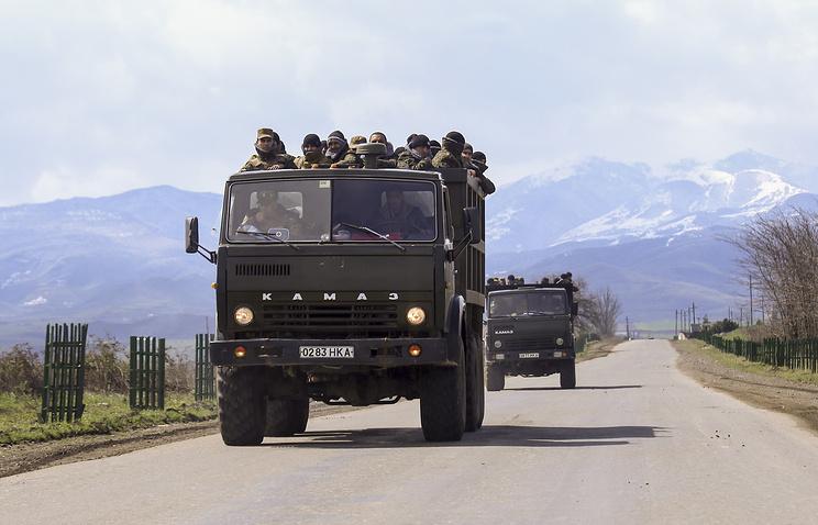 Armenian fighters stand in backs of Kamaz military trucks in the region of Nagorno-Karabakh, Azerbaijan