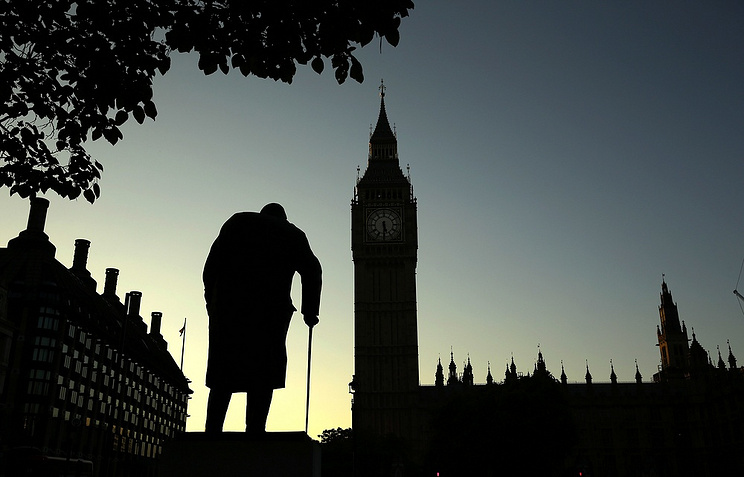 A statue of Winston Churchill silhouetted against the Houses of Parliament in London