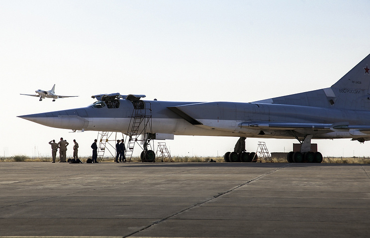 a Russian Tu-22M3 bomber stands on the tarmac while another plane lands at an air base near Hamedan, Iran