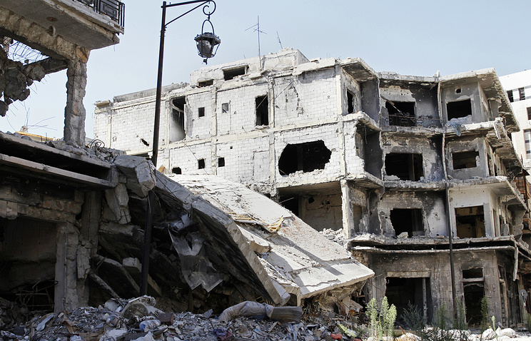 Damaged buildings and rubble line a street in Homs, Syria