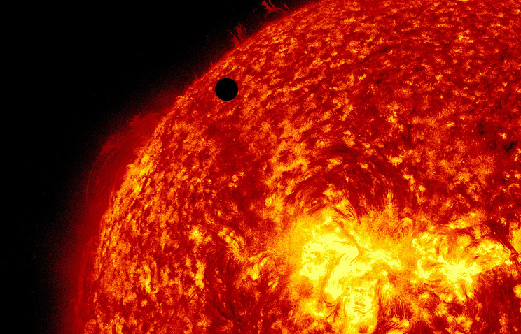 Planet Venus seen as a small black dot against the massive surface of the Sun