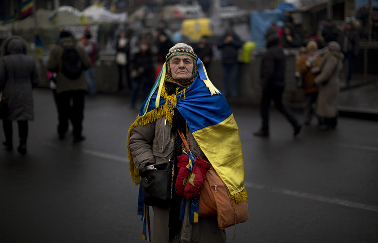Woman wearing an Ukrainian flag in Kiev's Independence Square