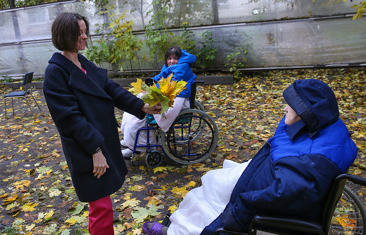 Volunteer takes patients for a walk at the Palliative care center in Moscow