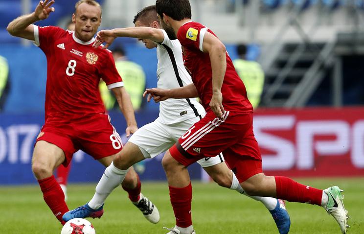 New Zealand's attacking midfielder Marco Rojas (center) vies for the ball against Denis Glushakov (left) and Georgi Dzhikiya (right)