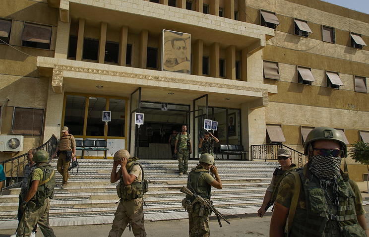 Russian military police soldiers walk out side a hospital in Deir el-Zor, Syria