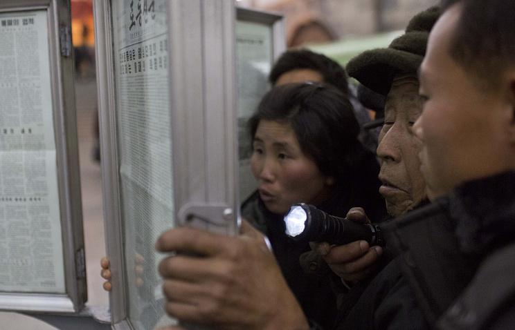 Жители Пхеньяна читают газеты о казни Чан Сон Тхэка