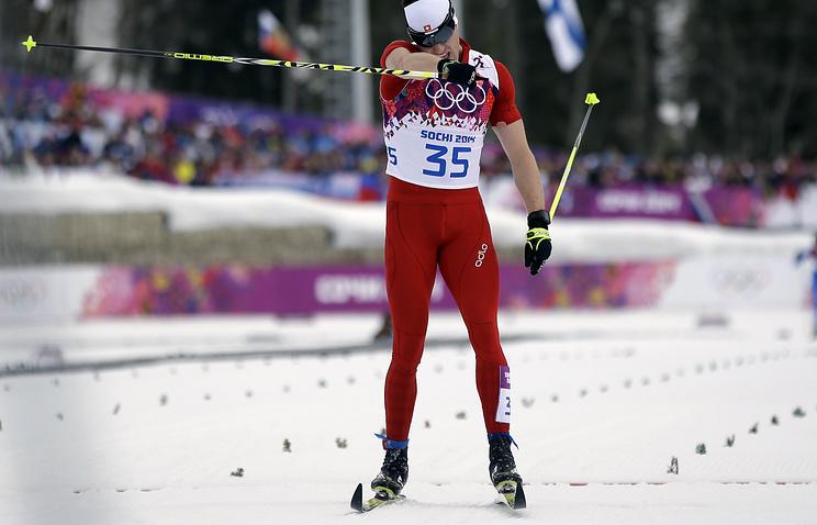 Швейцарский лыжник Дарио Колонья на финише в индивидуальной гонке на 15 км