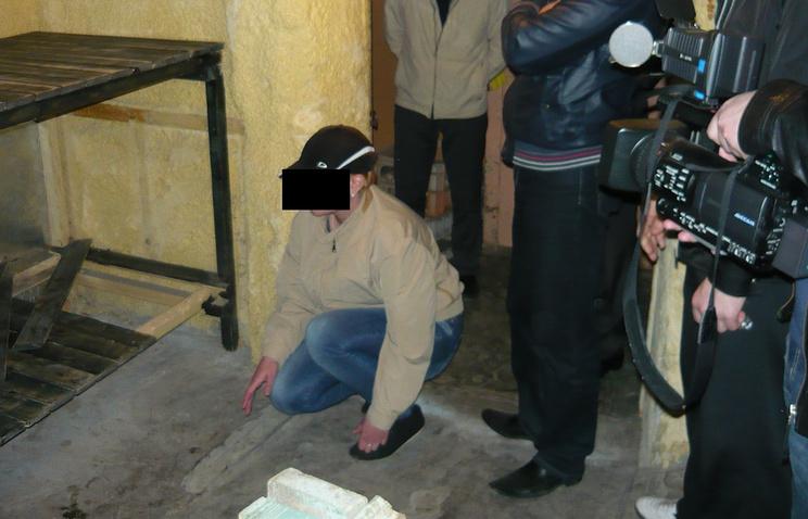 Подсудимая во время следственного эксперимента показывает место, куда она положила тела убитых детей