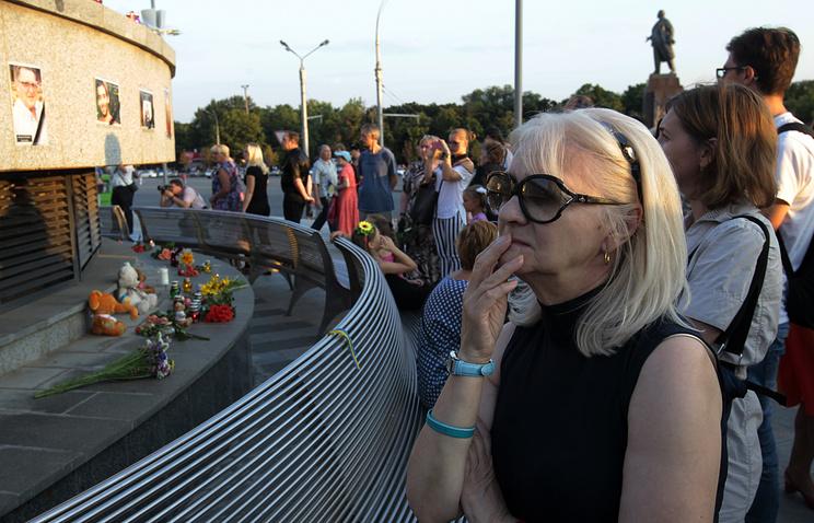 Люди смотрят на фотографии погибших в авиакатастрофе на Украине