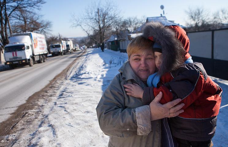 Женщина с ребенком встречают конвой с гуманитарной помощью в Донецке