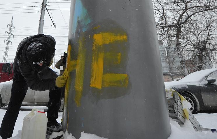 Мужчина отмывает памятник Ленину в Новосибирске, который был раскрашен в цвета национального флага Украины