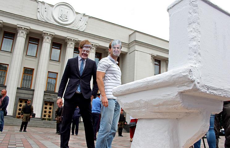 Активисты в масках генерального прокурора Украины Виктора Шокина и президента Украины Петра Порошенко во время акции у здания Верховной рады