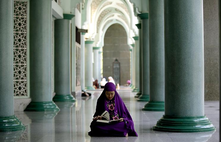 Мусульманка читает Коран в первый день Рамадана 2015 года в пригороде столицы Индонезии Джакарты