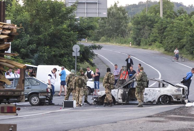 """Сотрудники милиции около сгоревшего автомобиля после перестрелки между бойцами """"Правого сектора"""" и представителями силовых структур"""