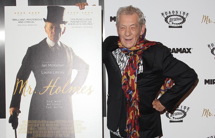 """Иэн Маккелен с постером к фильму """"Мистер Холмс""""."""