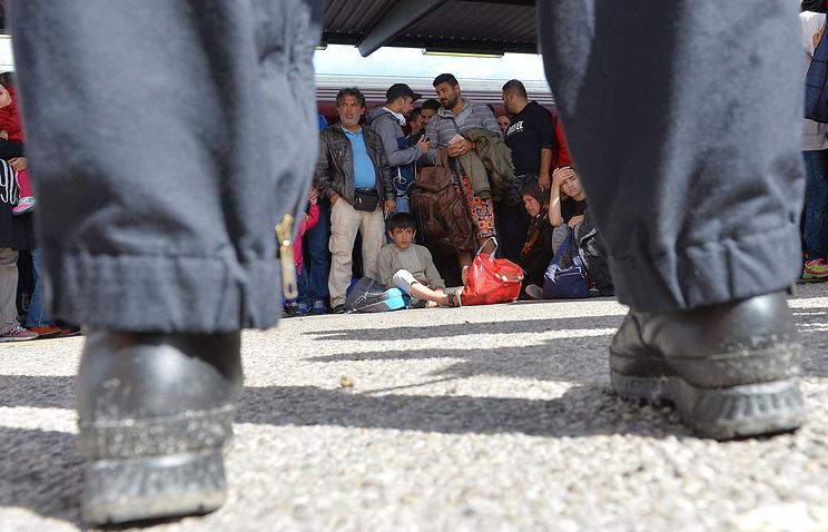 Беженцы на вокзале в Германии после того, как полиция остановила поезд, направляющийся из Австрии в Фрайлассинг, Германию