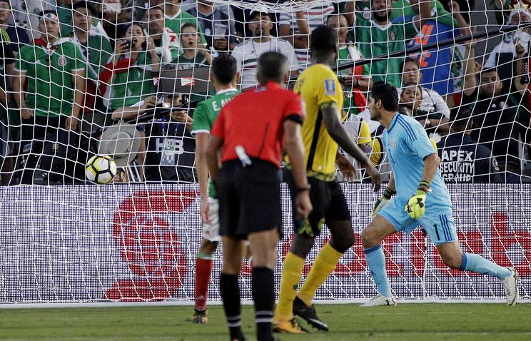 Кемар Лоуренс (в желтой форме) отправляет мяч в ворота сборной Мексики
