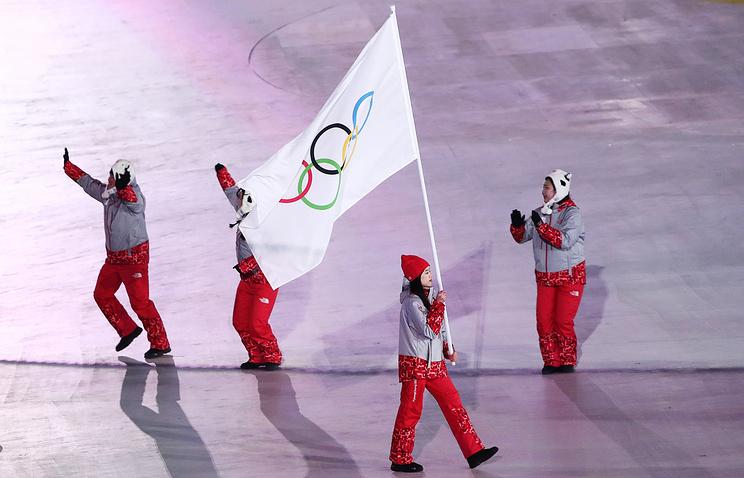 Волонтер Хон Хе Лин с олимпийским флагом на церемонии открытия Игр-2018