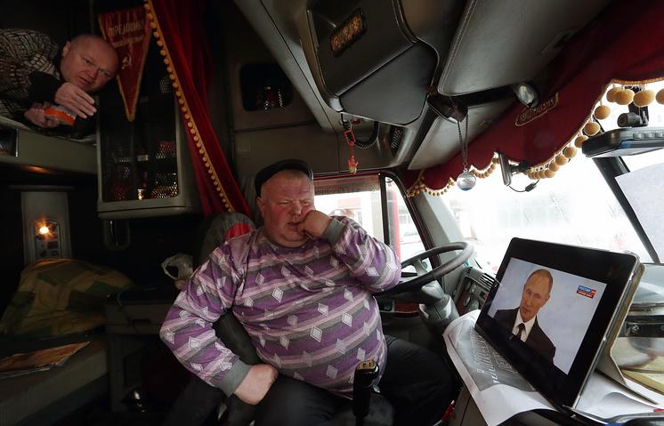 A Russian truck driver listening to Vladimir Putin's address