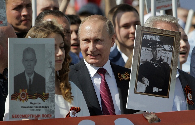 President Vladimir Putin holds a portrait of his father Vladimir Spiridonovich Putin who fought in World War II during the Immortal Regiment march in Moscow