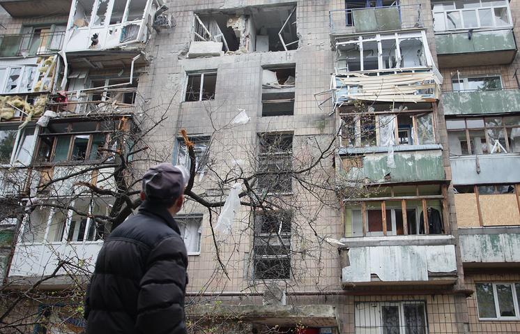 Сотрудники ОБСЕ дома, пострадавшего в результате обстрелов Киевского района