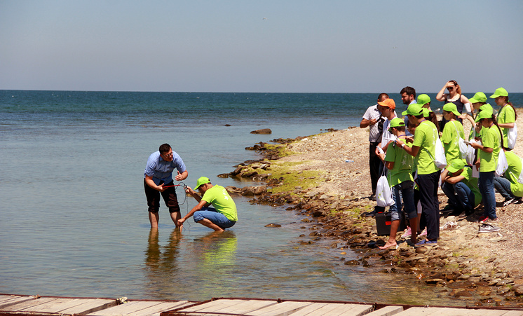 """Группа по направлению """"биология"""" вместе с учителем Александром Мерщиевым исследуют воду Каспийского моря рядом с лагерем"""